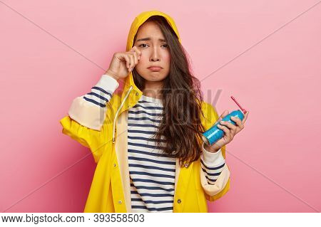 Dejected Asian Woman Cries From Despair, Rubs Eye Holds Bottle Of Spray, Wears Yellow Raincoat, Pose