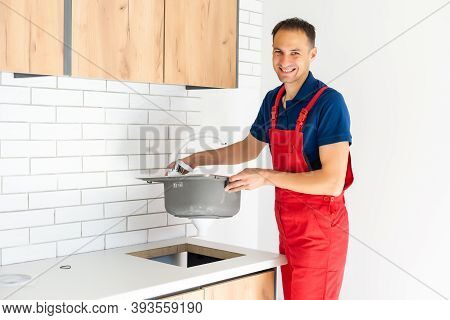Plumber Putting A Silicone Sealant To Installing A Kitchen Sink