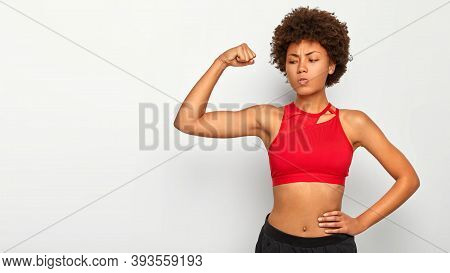Serious African American Woman Shows Muscles, Keeps One Hand On Waist, Demonstrates Her Strength And