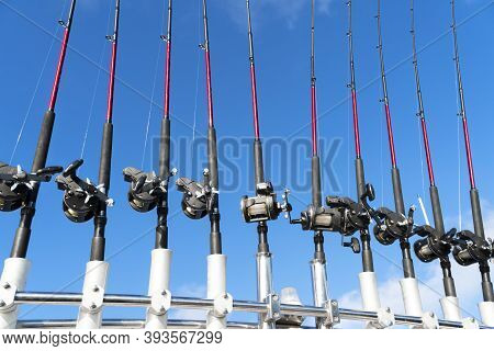 Fishing Trolling Boat Rods In Rod Holder. Big Game Fishing. Fishing Reels And Rods Pattern On Boat.