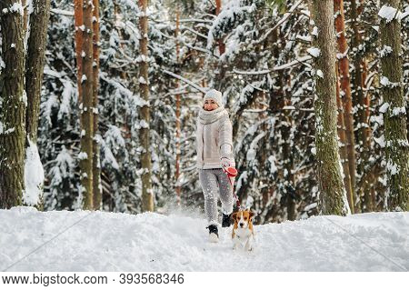 A Woman On A Walk With Her Dog In The Winter Forest. Mistress And Dog Game In The Snowy Forest.