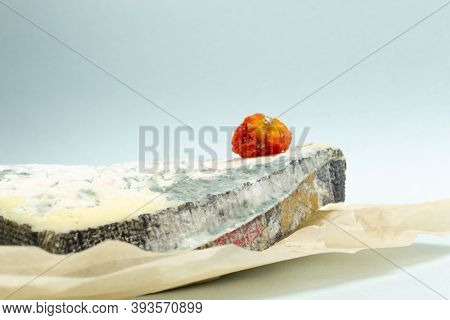 Several Pieces Of Spoiled Cheese With Spoiled Cherry Tomato On A Blue Background. Food Waste Concept