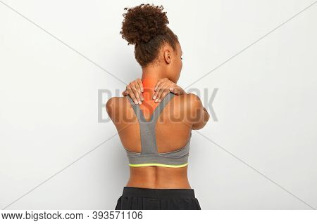 Curly Haired Young Afro Woman Massages Tense Muscles, Has Pain In Neck And Spasm, Dark Skin, Wears S