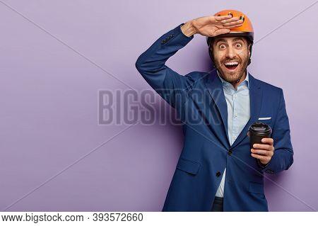 Photo Of Happy European Guy Keeps Palm Near Forehead, Drinks Takeout Coffee, Wears Headgear And Form