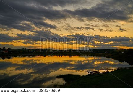 Beautiful, Colorful Sunset Sunrise Over A Lake. Crepuscular Rays And Clouds Reflected In Calm Water