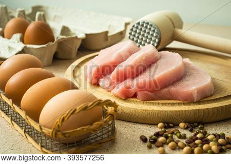 Raw Loin Meat On A Board, Meat Mallet And Eggs