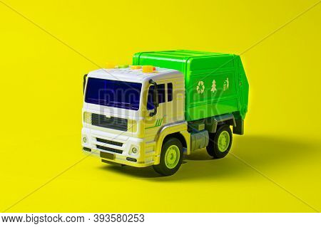 The Toy Garbage Truck White-green With A Yellow Background. Childrens Toy Car With Buttons. For The