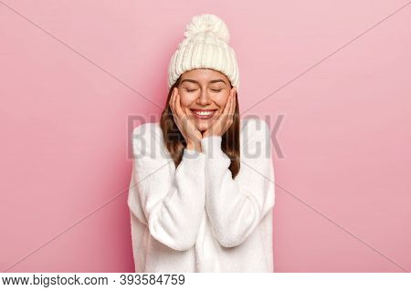 Tender Relaxed Carefree Woman With Toothy Smile, Wears White Casual Jumper And Hat, Feels Joyful And