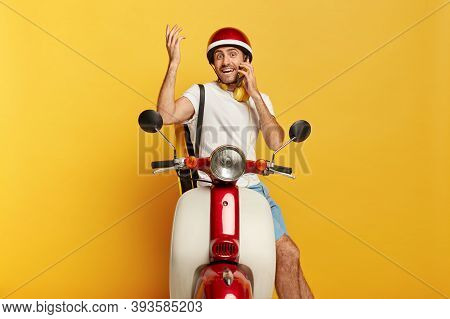 Ready To Ride. Happy Confused Male Rider Sits On Scooter, Has Telephone Conversation While Stops On