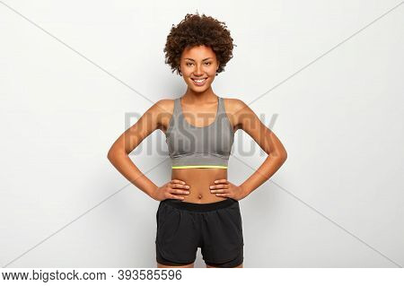 Photo Of Optimistic Dark Skinned Sporty Woman Keeps Hands On Waist, Smiles Happily, Dressed In Sport