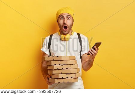 Amazed Deliveryman Receives Orders From Customers Via Smartphone, Holds Pile Of Cardboard Pizza Boxe
