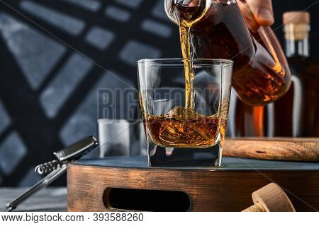 Square Glass Of Whiskey With Ice On A Tray, The Glass Is Filled With Whiskey From The Bottle. Square