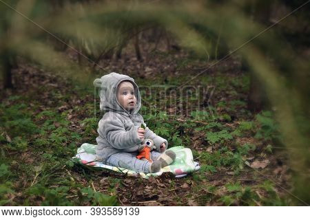Small Child Is Sitting On An Open Meadow In The Park. The Kid In The Evening Forest And In The Hood,