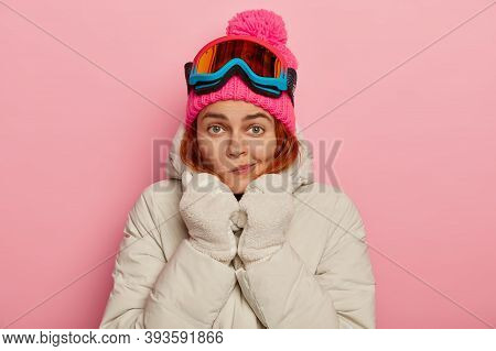 Photo Of Lovely European Female Traveler Purses Lips, Warms Herself In Comfortable Outerwear During
