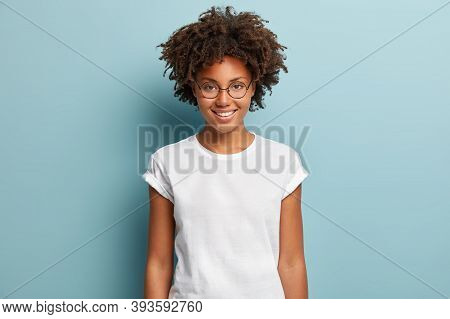 Waist Up Shot Of Happy Curly Woman With Toothy Smile, Wears Optical Glasses And Casual Solid White T