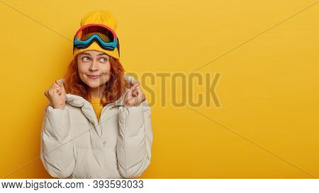 Thoughtful Female Tourist Recreats During Winter Time, Raises Fists, Anticipates For Miracle, Wears