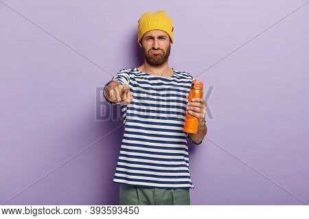 Displeased Unshaven Youngster Points Index Finger At Camera, Holds Thermos With Aromatic Beverage, H