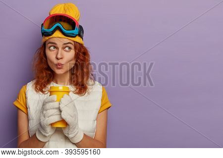 Portrait Of Pensive Redhead Woman Dressed In Casual Wear, Keeps Lips Rounded, Enjoys Aromatic Bevera