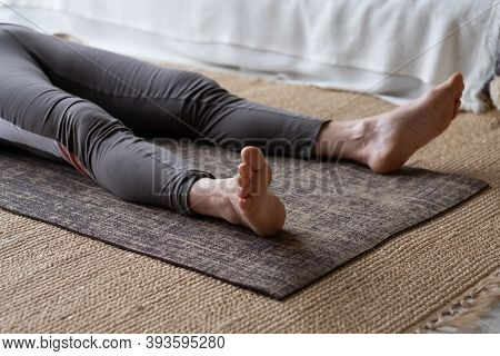 Woman Lying On Yoga Mat After Workout Relaxing On Floor At Home.