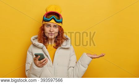 Relaxation, Winter And Pastime Concept. Confused Redhead Woman Tourist Holds Mobile Phone, Cannot He