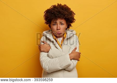Sad Discontent Curly Woman Feels Freezy, Trembles From Cold, Wears White Outerwear, Crosses Arms Ove