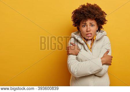 Dissatisfied Dark Skinned Woman Feels Frozen After Outdoor Walk During Frosty Weather, Wears Warm Wh