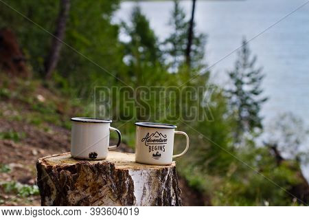 Two Metal Aluminum Enameled Mugs With Hot Tea With Steam On A Felled Wood Table In Summer On The Sho
