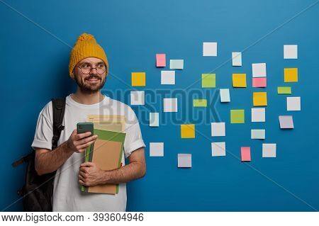 Handsome Bearded Youngster Stands With Textbooks, Mobile Phone And Rucksack, Sends Text Message To G