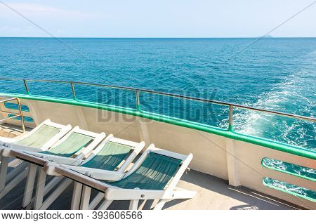 Empty Deck Chairs On The Upper Deck Of A Cruise Ship. Sun Loungers On The Sea Yacht For Relaxing