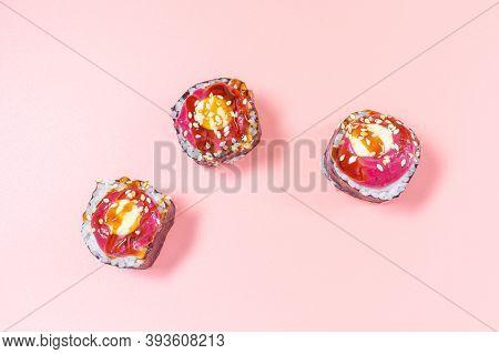 Original Rolls With Berry Sauce, Unagi Sauce, Sesame Seeds. Close-up, Pink Background, Top View. Con