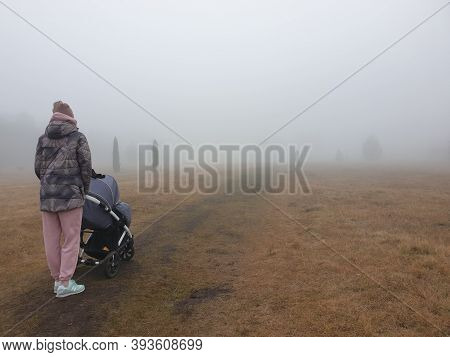 Mother With A Baby Carriage Walks In A Foggy Park. Woman With A Baby Carriage. Walk In The Autumn Pa
