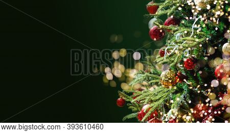 Decorated With Ornaments And Lights Christmas Tree On Green Background. Merry Christmas And Happy Ho