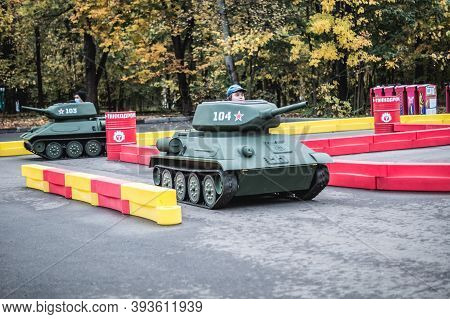Russia, Moscow - October 10, 2020: Young Boy Drives Toy Tank. Children Attraction In Vdnkh Park In M