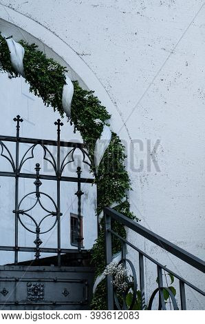 Arched Entrance To A Church With A Wrought Iron Gate Decorated With Box Twigs And White Flowers And