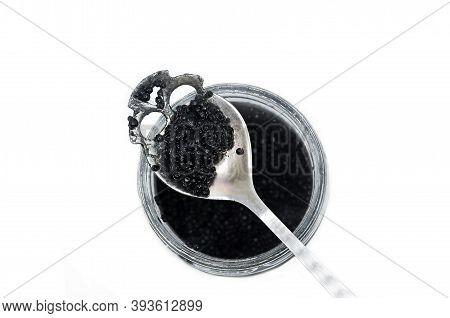 Black Sturgeon Caviar On A Spoon, Skull Shaped Spoon Isolated On White. Luxurious Black Caviar. Stur