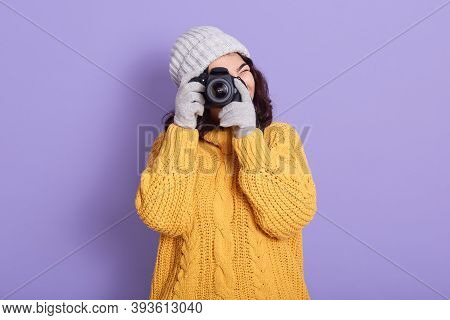 Young Brunette Photographer Taking Photos Isolated On Lilac Background, Wearing Yellow Sweater, Cap