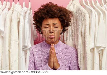 Calm Curly Woman Keeps Palms Pressed Together, Prays For Wellbeing, Wears Knitted Sweater, Stands Be