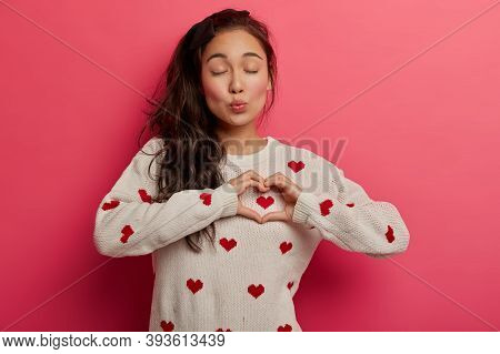 Charming Woman With Folded Lips Shows Heart Gesture Over Chest, Expresses Heartwarming Feelings, Sym