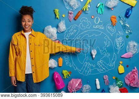Positive Dark Skinned Woman Demonstrates Her Plan About Cleaning Earth, Points At Ligh Bulb In Cente