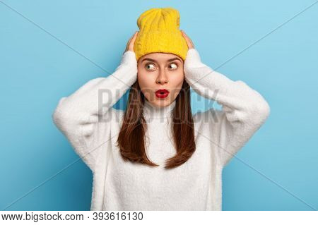 Scared Beautiful Young Woman Keeps Both Hands On Head, Looks Aside With Terror, Has Long Dark Hair,