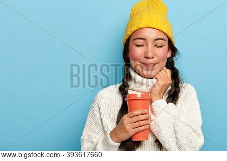 Studio Shot Of Pleasant Looking Asian Woman Has Two Plaits, Wears Yellow Hat And White Oversized Swe