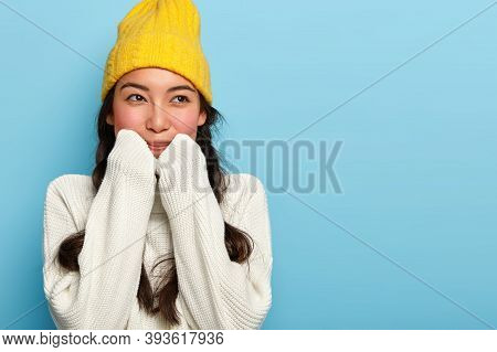 Indoor Shot Of Lovely Brunette Woman Wears Yellow Hat And White Sweater, Ready For Winter Stroll Wit