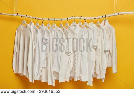 Group Of White Plain Clothes Hanging On Garment Rack Or Rail. Minimalistic Concept. Apparel For Wome