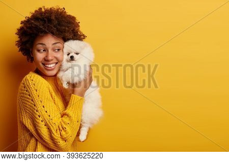 Studio Shot Of Glad Woman Holds Spitz Dog Near Face, Has Happy Mood, Likes Loyal Devoted Domestic An