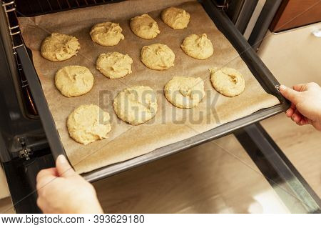 The Woman Sends A Baking Sheet Of Raw Cookies To The Oven For Baking.