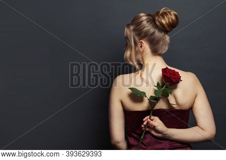 Beautiful Woman Back Head With Blonde Hair Updo Hairdo Holding Red Rose Flower On Black