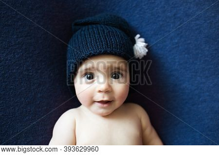 Cute Newborn Baby In The Dark Blue Hat. Happy Baby On A Dark Blue Background. Closeup Portrait Of Ne