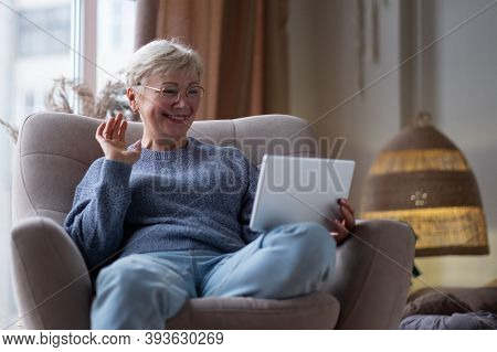 Smiling Mature Mother Holds Tablet And Waves Her Hand At Home.