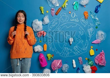 Young Curly Female Activist Holds Two Plaits, Looks Aside, Demonstrates Problem Of Plastic Pollution