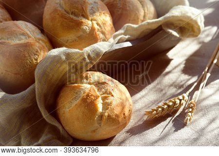 Close-up On Rusty Round Bun, Kaiser Or Vienna Rolls On Table Covered With Linen Tablecloth
